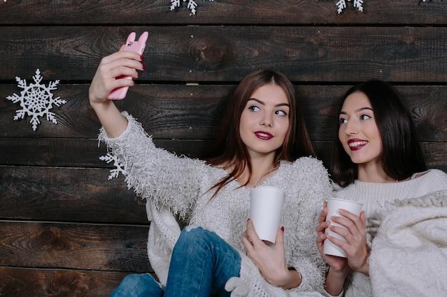 Две симпатичные молодые смешные женщины друзья улыбаются и веселятся, делают салфи Бесплатные Фотографии