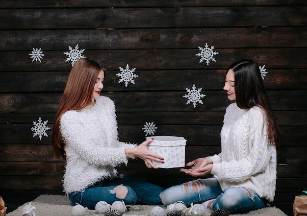 Due amici di donne divertenti abbastanza giovani che sorridono e si divertono, che tengono i regali di festa luminosi, pronti per la celebrazione. Foto Gratuite