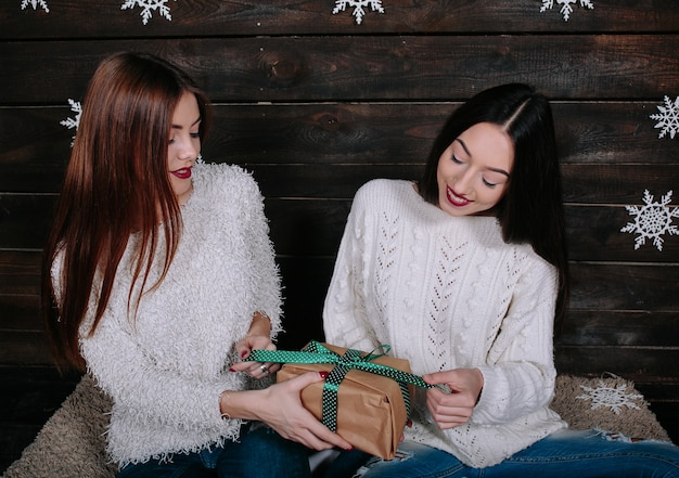 Due amici donne divertenti abbastanza giovani che sorridono e che si divertono, che tengono i regali di festa Foto Gratuite