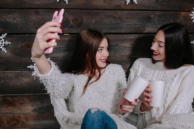 Due amici di donne divertenti abbastanza giovani sorridenti e divertendosi, fanno salfie Foto Gratuite