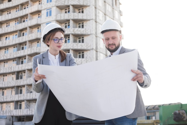 Two professional architect holding blueprint and looking at it near construction site Free Photo