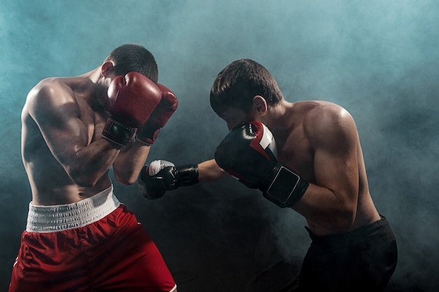 Two professional boxer boxing on black smoky Free Photo