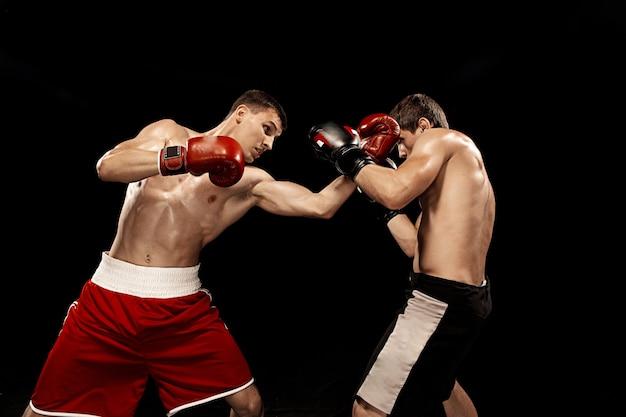 Due pugili professionisti boxe sulla parete nera Foto Gratuite