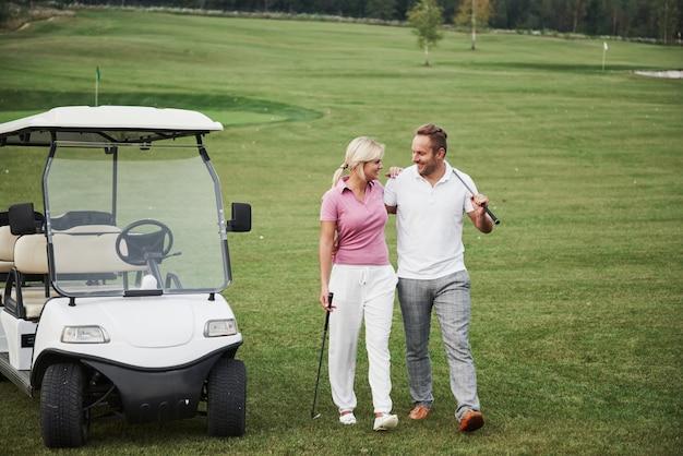 두 명의 프로 골퍼, 여자와 남자가 다음 홀로갑니다. 연인들은 안아주고 웃으며 데이트를 해요 프리미엄 사진