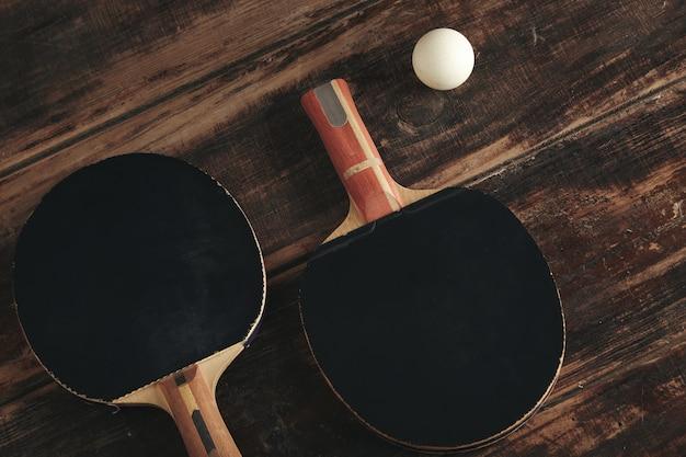 Due razzi di ping pong professionali che si trovano sulla tavola di legno dell'annata. Foto Gratuite