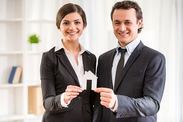Two realtors in suits are showing a model of house. Premium Photo