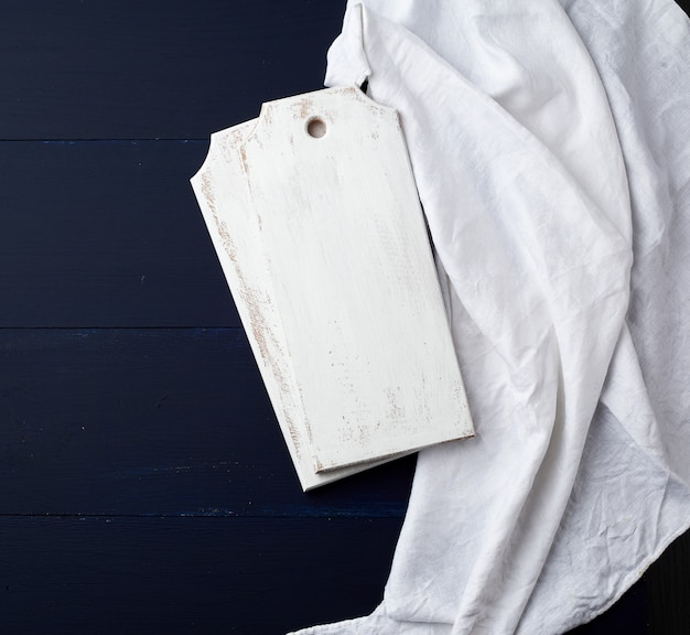 Two rectangular white cutting kitchen boards on a blue wooden , next to a white textile towel, top view Premium Photo