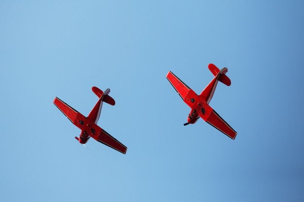 Two red airplanes in blue sky Premium Photo