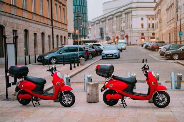 Two red electric motorbikes for rental parked on the street Premium Photo