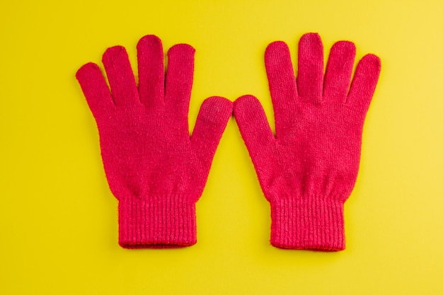 Two red gloves isolated on yellow Premium Photo