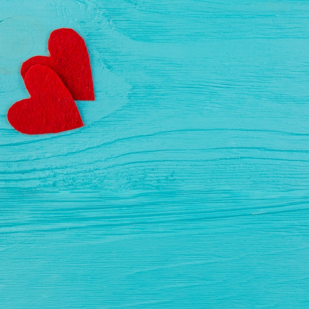 Two red hearts on blue wooden surface Free Photo