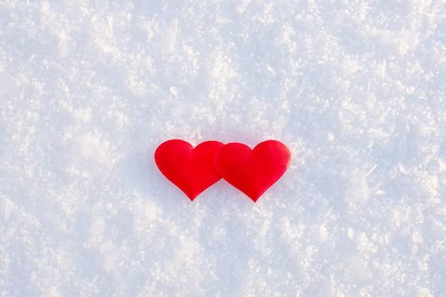 Два красных сердца, лежащих на белом чистом снегу в солнечный зимний день. Premium Фотографии