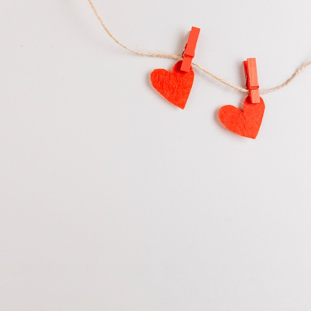 Two red hearts on string with pins Free Photo