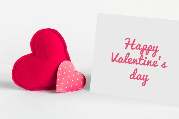 Two red hearts and a white sheet of paper with inscription happy valentine's day Premium Photo