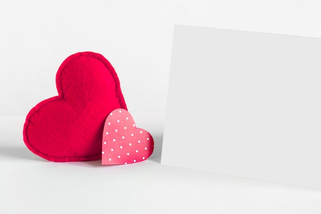 Two red hearts and a white sheet of paper Premium Photo