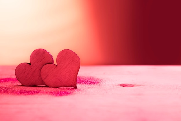 Two red hearts with glitter on pink table Premium Photo