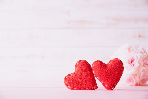 Two red hearts with pink rose flower on wooden background. Premium Photo