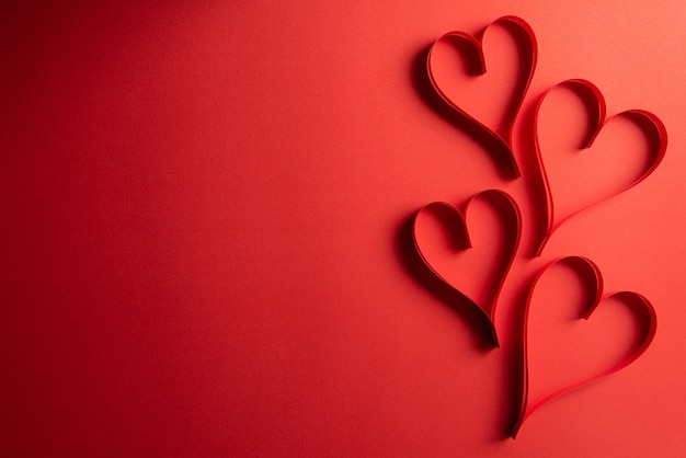 Two red paper hearts on red Premium Photo