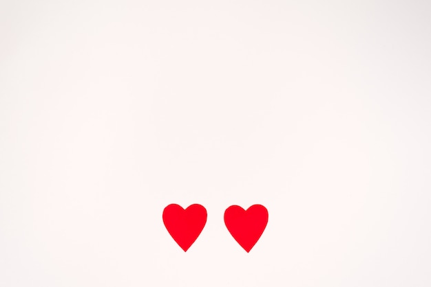 Two red paper hearts on a white background, copying space. valentine's day holiday card Premium Photo