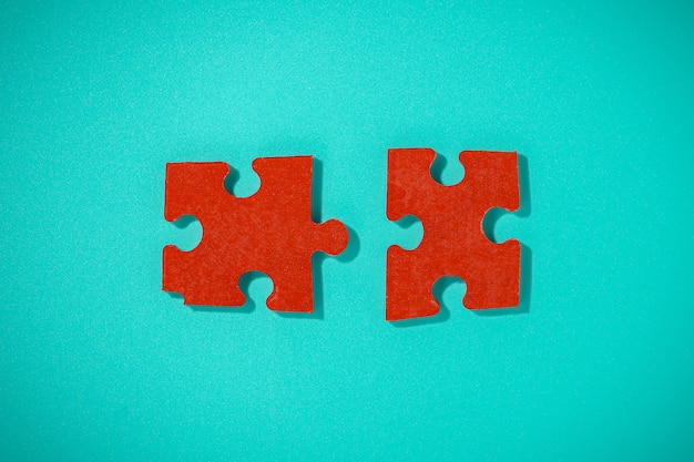 Two red piece flat puzzle jigsaw on blue table Premium Photo
