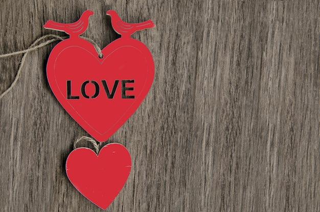 Два сердца в форме сердца с двумя голубями на деревянном фоне Premium Фотографии