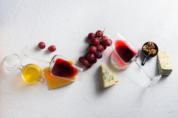 Два бокала красного вина с ассорти сыров Premium Фотографии
