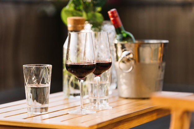 Two red wine glasses and glass of water on wooden table Free Photo