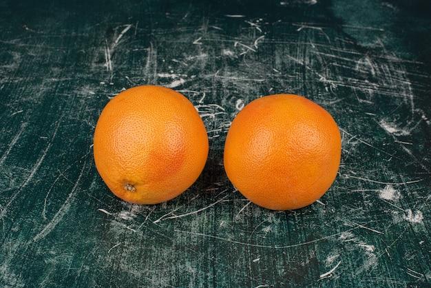 Due arance mature sulla superficie di marmo. Foto Gratuite