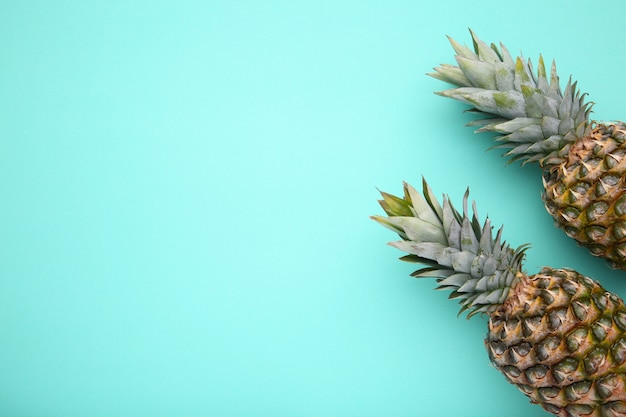 Two ripe pineapples on a mint background Premium Photo