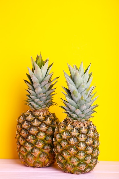 Two ripe pineapples on a yellow background Premium Photo