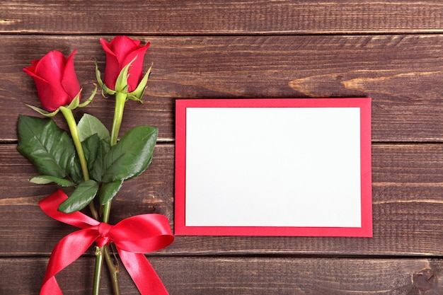 Two roses and a valentine card on wood Free Photo