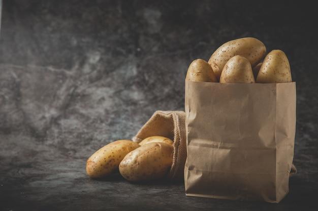 Two sacks full of potatoes on gray floor Free Photo