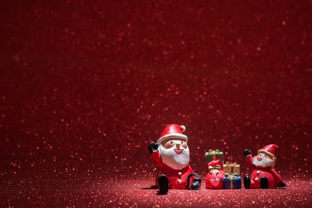 Two santa claus with shiny red background Free Photo