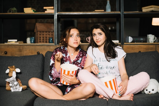 Two scared women sitting on sofa with popcorn watching television Free Photo