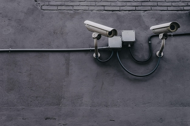 Two security cameras on a grey wall Free Photo