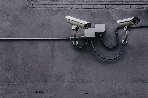 灰色の壁に2つの防犯カメラ 無料写真