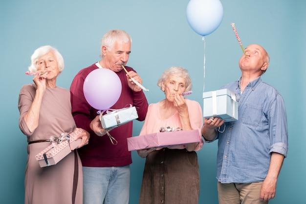 Две пожилые пары с подарочными коробками свистят в свисток во время празднования дня рождения Premium Фотографии