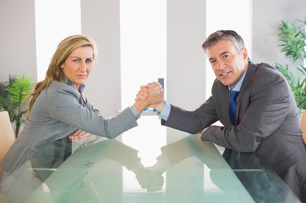Two serious businesspeople having an arm wrestling sitting around a table Premium Photo