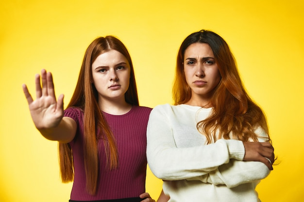 Two serious redhead caucasian girls are standing shoulder to shoulder Free Photo
