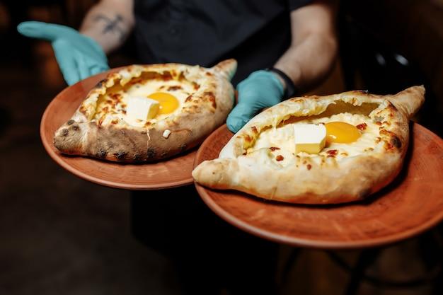 チーズとバターを使ったやわらかい柔らかい生地のハチャプリ2皿。黒い手袋をしたウェイターの手は、チーズと卵を添えた2つの伝統的なハチャプリを持っています。 Premium写真