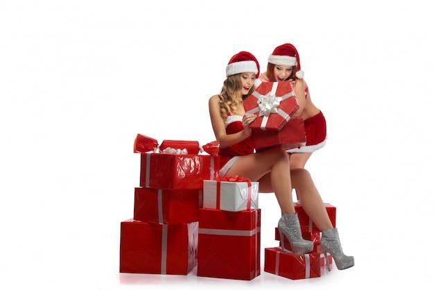 Две сексуальные рождественские девушки позируют с кучей подарков Бесплатные Фотографии