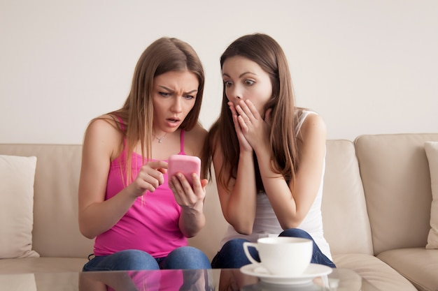 Two shocked young girls looking at smartphone screen. Free Photo