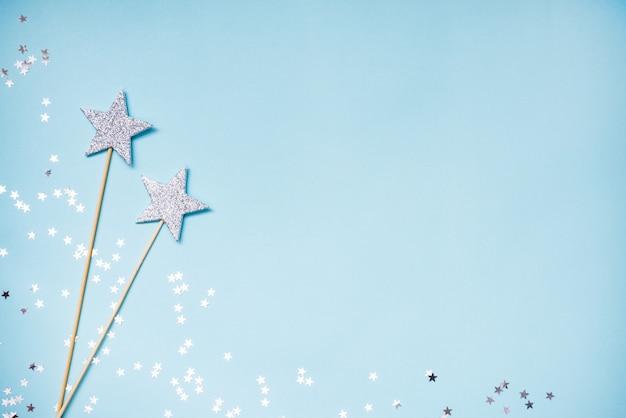 Две серебряные волшебные палочки и разбросанные блестки на синем фоне. копировать пространство Premium Фотографии