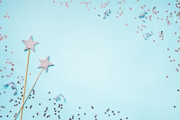 Две серебряные партии волшебные палочки, блестки и ленты на синем фоне. копировать пространство Premium Фотографии