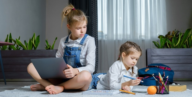 Two sisters lying on the floor at living room using laptop, playing and drawing Premium Photo
