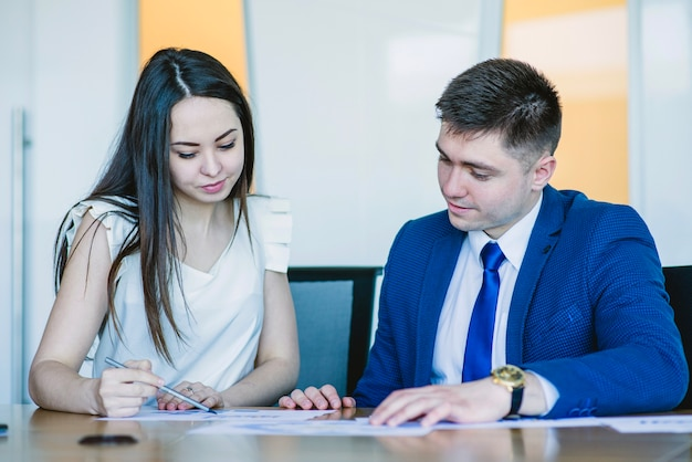 Two sitting business people looking at documents Free Photo