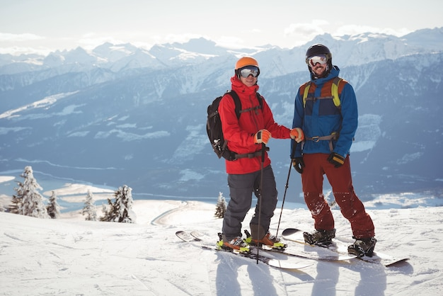 Two skiers standing together on snow covered mountain Free Photo