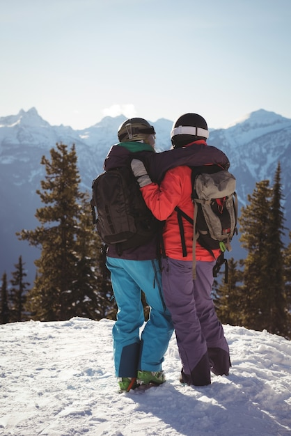 Two skiers standing together with arm around on snow covered mountain Free Photo