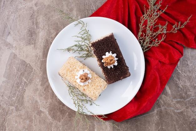 Due fette di torte sul piatto bianco con tovaglia rossa. Foto Gratuite
