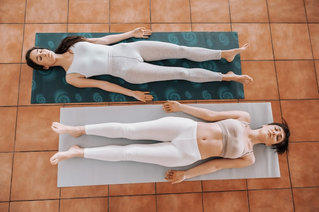 Two slim young women lying on the backs on mat barefoot in corpse yoga position and relaxing. Premium Photo